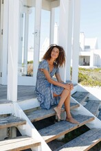 Woman Relaxing On Steps In Front Of Beach House