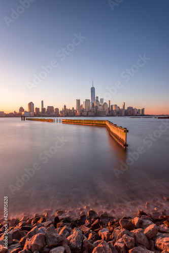 Foto Murales View across the water of New York City, Manhattan island, at dawn, flat calm water.