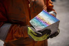 Worker Holding Fractured Block Of Titanium Alloy With Coloured Iridescence In Titanium Recycling Plant