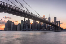 View Of Brooklyn Bridge To New York City, Manhattan Island, At Dawn, Flat Calm Water.