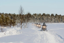 Tourists Driving Snowmobiles In The Forest Near Jukkasjarvi, Sweden