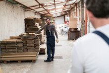 Worker Resting Hand On Stack Of Cardboard Boxes In Factory