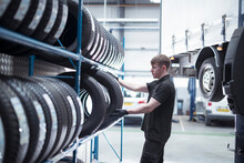 Apprentice Engineer Selecting Tyres In Car Service Centre