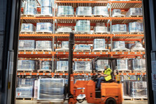 Fork Lift Truck Driving Past Printed Food Packaging In Storage In Print Factory