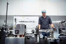 Worker Adjusting Printing Machine In Print Factory