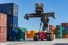 Reach Stacker And Shipping Containers In Dock