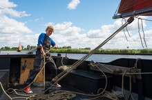 Girl Stands At Helm Of Large Flat-bottom Traditional Sailing Ship,