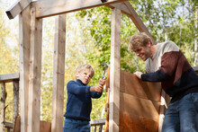 Father And Son Building Treehouse Together In Garden
