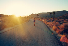 Woman Jogging On Country Road At Sunset, Joshua Tree, California, USA
