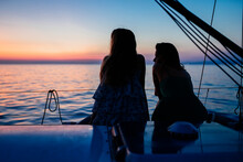 Friends Watching Sunset On Sailboat, Italy