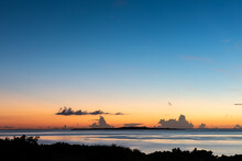 Peaceful Sunrise In Blue, Orange And Yellow Colors, Serene Sea And The Beautiful Island Of Hatoma Composing The Background. Iriomote Island.
