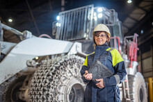 Portrait Of Female Steelworker And Dumper Truck In Steelworks