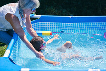Grandmother Supporting Granddaughter In Pool