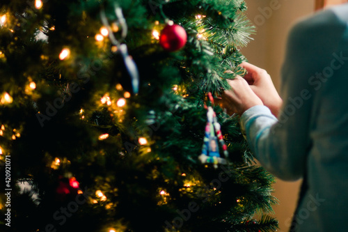 Person decorating Christmas tree at home