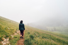 Woman Hiking On Hilltop, Thick Fog In Background