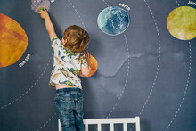 Toddler Playing With Toy On Wall With Mural Of Solar System