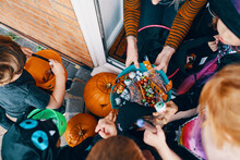 Overhead View  Of A Group Of Children At A Front Door Taking Sweets From A Bowl At Halloween.