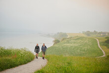 Two People Walking Along A Coastal Path