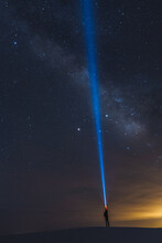 Man Shining Torch Into Sky, White Sands National Monument, New Mexico, US