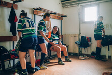 Four Women Wearing Blue, White And Green Rugby Shirts In A Dressing Room.