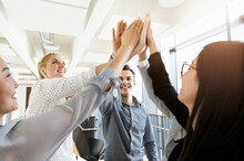 Colleagues Giving High Five In Office
