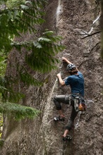 A Trad Climber In Helmet With Limited Equipment, Climbing Up A Sheer Cliff Face In Pine Trees.
