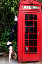 Young Woman In Handstand Next To A Red Telephone Box On A London Street.