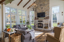 Interior View Of Living Room With Dark Grey Sofas, Rug And Stained Oak Wood Floorboards Inside Country Style Home, Quebec, Canada.