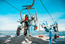Two People Sitting On A Ski Lift Wearing Ski Suits, Helmets And Goggles, Holding Snowboards And Ski Poles, View Across The Mountains In The Background.