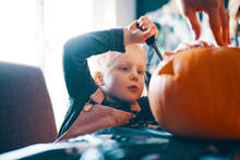 A Girl Concentrating And Cutting A Face In A Pumpkin.