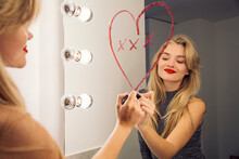 A Woman Looking In A Bathroom Mirror Drawing A Heart On The Mirror With Lipstick.