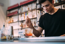 Young Man Wearing Black Clothes Standing Behind Bar Counter, Preparing Drink.