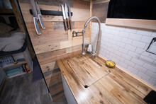 Kitchen Area In The Campervan With A Wooden Worksurface And Inset Sink, Wood Clad Wall And White Tiled Splashback.
