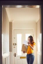 Teenage Girl Standing In Hallway Holding Large Envelope With Letter.