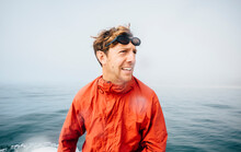 Portrait Of Man Wearing Orange Jacket On An Inflatable Dingy In Pacific Ocean.