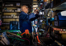 An Ironmonger, Elderly Man In A Boiler Suit Searching Through Shelves Stacked With Useful Household Items And Tools.