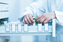 Close Up Of Pharmacist Standing Next To A Drawer With Medicines In Pharmacy.