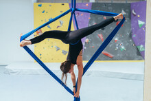 Female Acrobat Practicing, Suspended From Blue Silk.
