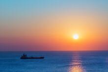 Cargo Ship And Sunrise Over The Mediterranean Sea.
