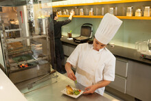 Female Chef Wearing Chef's Hat Standing At Worktop In Commercial  Kitchen, Garnishing Plate Of Food.