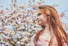 Portrait Of Brunette Girl Standing Outdoors, Tree With Pink Blossoms In Background.