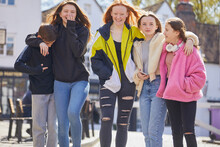 Group Of Teenage Girls And Boy Walking Side By Side Outdoors.
