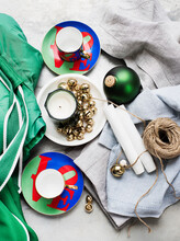 Overhead View Of Coffee Cups And Saucers, Candles, Bells, Linen Napkins And A Ball Of String.