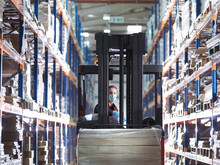 Man Wearing Surgical Face Mask And High Visibility Vest Working In A Large Warehouse.