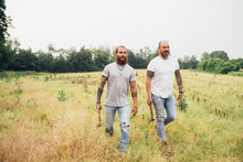 Two Bearded Tattooed Men With Long Brunette Hair Walking Across A Meadow, Carrying Axes.