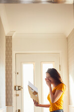 Teenage Girl Standing In Hallway Holding Large Envelope With Letter, Laughing.