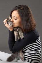 Studio Shot Of Woman Hugging Grey Cat, On Grey Background.