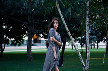 Portrait Of Woman With Long Brown Hair, Wearing Long Patterned Wrap Dress, Standing In A Park.