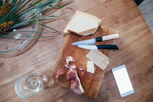 High Angle Close Up Of Knives, Smoked Ham And Hard Cheese On Wooden Cutting Board.