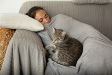 Woman And Grey Tabby Cat Sleeping On A Sofa.